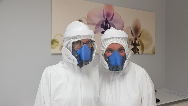 Personel gabinetu w maskach i kombinezonach ochronnych
